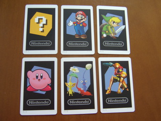 The six included AR Cards. One with a question mark (for activating the minigames), and the others, featuring Mario, Link, Kirby, Pikmin and Samus
